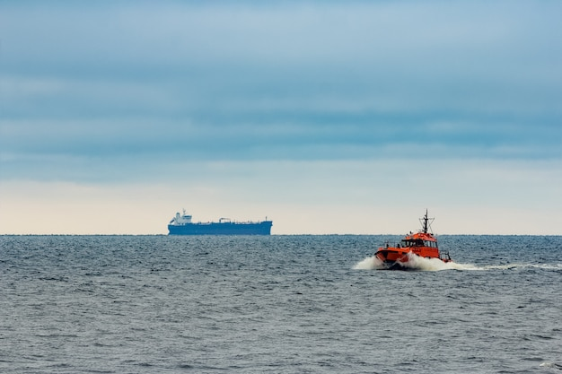 Czerwony statek pilotowy poruszający się z prędkością na morzu bałtyckim