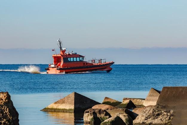 Czerwony statek pilotowy poruszający się z prędkością obok tamy falochronu