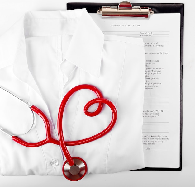 Czerwony stetoskop, dokumentacja medyczna i jednolity na białej powierzchni