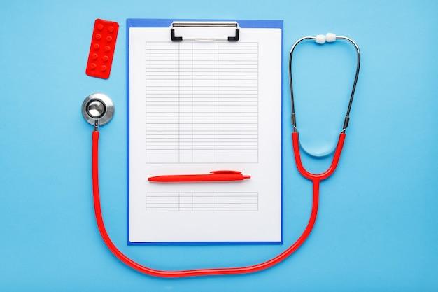 Czerwony stetoskop, medyczne maski higieniczne tabletki dokumenty medyczne na miejscu pracy lekarzy.