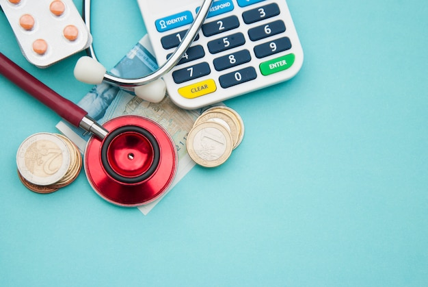 Czerwony stetoskop na stosie monet, pigułki na niebiesko. copyspace. medycyna i opieka zdrowotna.