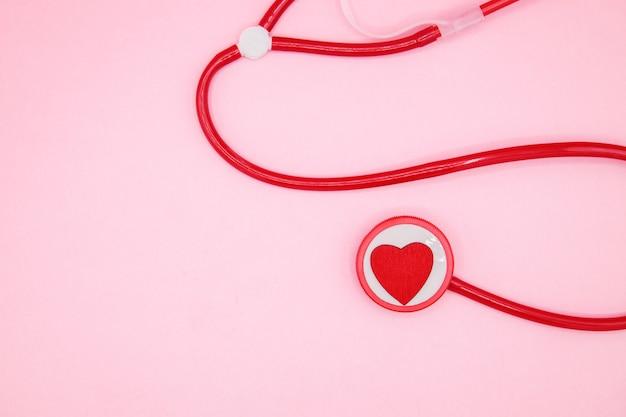 Czerwony stetoskop z sercem na różowym tle