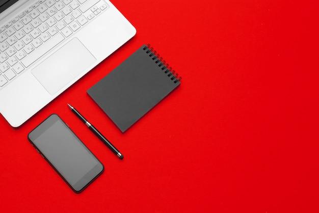 Czerwony stół biurkowy z artykułami biurowymi i materiałami biurowymi