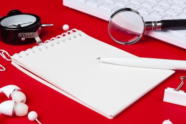 Czerwony stół biurkowy z pustym notatnikiem, klawiaturą i materiałami eksploatacyjnymi. widok z góry z lato. leżał płasko.