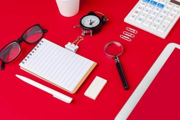 Czerwony stół biurkowy z pustym notatnikiem, klawiaturą i materiałami eksploatacyjnymi. widok z góry z miejsca kopiowania. leżał płasko.