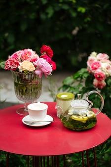 Czerwony stół z zestawem herbaty i kwiatami w ogrodzie