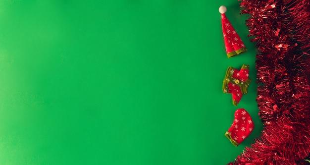 Czerwony świąteczny blichtr z ozdobnymi ubraniami świątecznymi. skopiuj miejsce. selektywne skupienie.