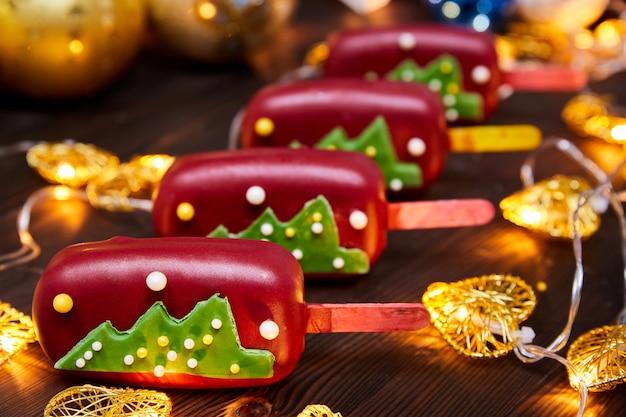 Czerwony świąteczny deser w formie musu na patyku ozdobiony choinką