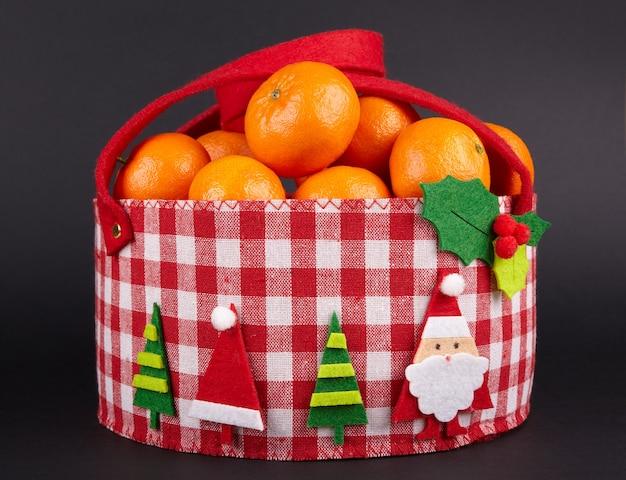 Czerwony świąteczny koszyk w klatce z aplikacją z mandarynek clementine