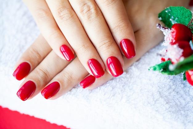Czerwony świąteczny manicure robi w studiu kosmetycznym