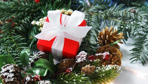 Czerwony świąteczny prezent położony w dekoracjach