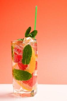 Czerwony świeży napój z lodem, grejpfrutem i mennicą na pomarańczowym tle. miejsce na tekst lub projekt.