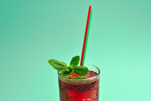 Czerwony świeży napój z lodem, grejpfrutem i mennicą na zielonym tle. miejsce na tekst lub projekt.