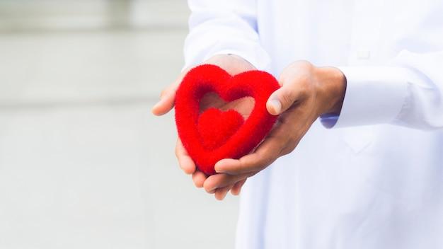 Czerwony symbol serca na ręce kapłana lub ręki mężczyzny