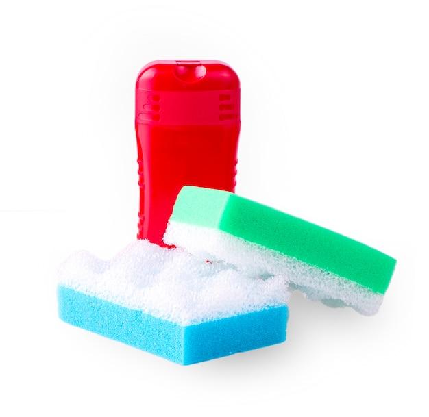 Czerwony szampon i dwie kolorowe gąbki do ciała na białym