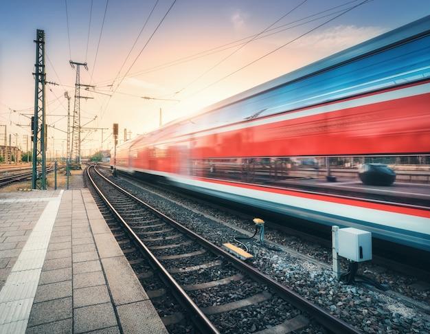 Czerwony szybki pociąg w ruchu na stacji kolejowej