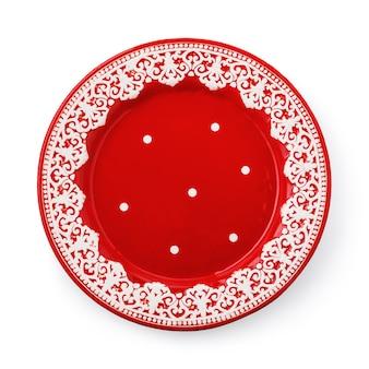 Czerwony talerz ceramiczny z białym wzorem na białym tle
