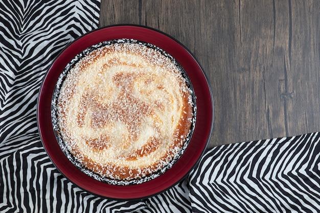 Czerwony talerz pysznego ciasta pudrowanego cukrem ułożony na obrusie.