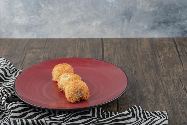Czerwony talerz pysznych wypieków kadaif umieszczonych na drewnianym stole.