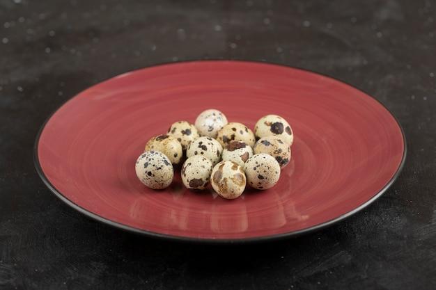 Czerwony talerz surowych świeżych jaj przepiórczych na czarnej powierzchni.