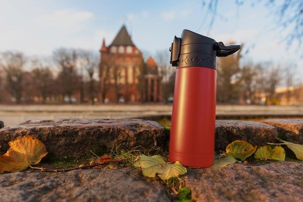 Czerwony termos na ulicy miasta jesienią.