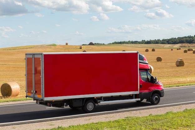 Czerwony tor dostawy, furgonetka na autostradzie, na żółtym polu pszenicy. jest miejsce na reklamę