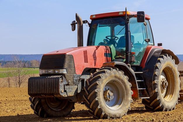 Czerwony traktor na polu rolnym w słoneczny wiosenny dzień.