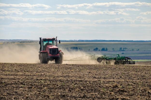 Czerwony traktor rolniczy w chmurze kurzu uprawia glebę na polu za pomocą kultywatora po żniwach letni słoneczny dzień żyzna ziemia nowoczesne maszyny rolnicze kopia przestrzeń