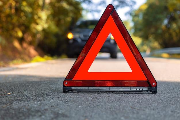 Czerwony trójkąt, czerwony znak stopu awaryjnego, czerwony symbol awaryjny i czarny samochód zatrzymujący się i zaparkuj na drodze.