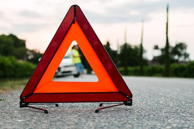 Czerwony trójkąt ostrzegawczy i młody człowiek za pomocą swojego telefonu komórkowego, aby zadzwonić do pomocy samochodu. skoncentruj się na czerwonym trójkącie!
