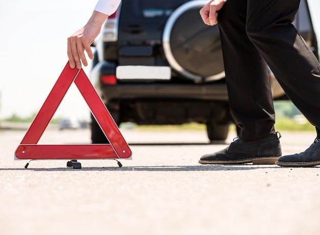Czerwony trójkąt ostrzegawczy z rozbitym samochodem na drodze.