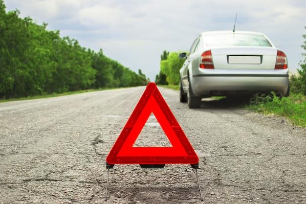 Czerwony trójkąt samochodu na drodze. trójkąt ostrzegawczy samochodu na drodze przed miastem wieczorem. awaria samochodu przy złej pogodzie.