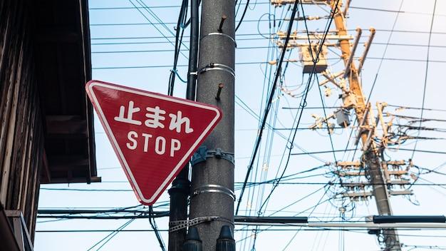 Czerwony trójkątny znak drogowy ostrzegający o ruchu drogowym z białymi literami kanji stojący na lokalnym skrzyżowaniu ulic w japonii. tłumaczenie tego słowa w języku japońskim oznacza stop
