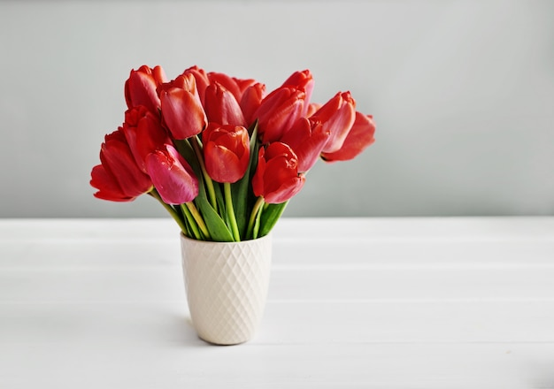 Czerwony tulipanowy kwiat odizolowywający na biel ścianie