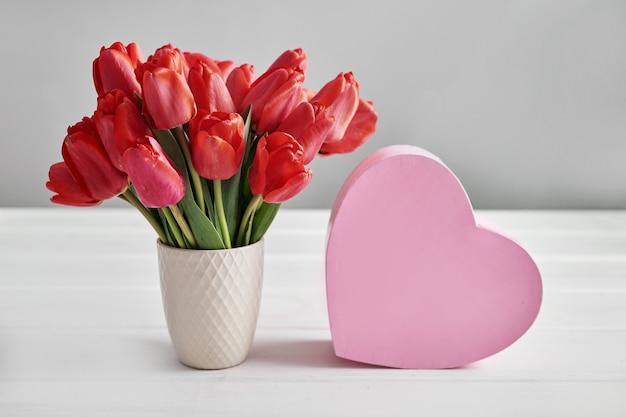 Czerwony tulipanowy kwiatu i prezenta pudełko odizolowywający na bielu stole.