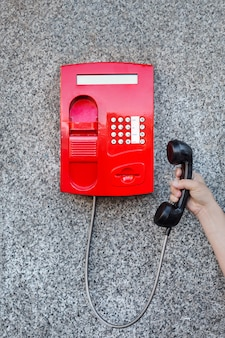 Czerwony uliczny telefon na ścianie i ręka mężczyzny podnosząca telefon
