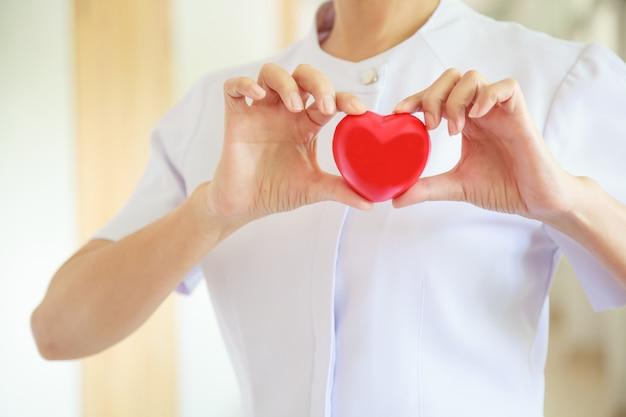 Czerwony uśmiechnięty serce trzymający żeńską pielęgniarką obiema rękami