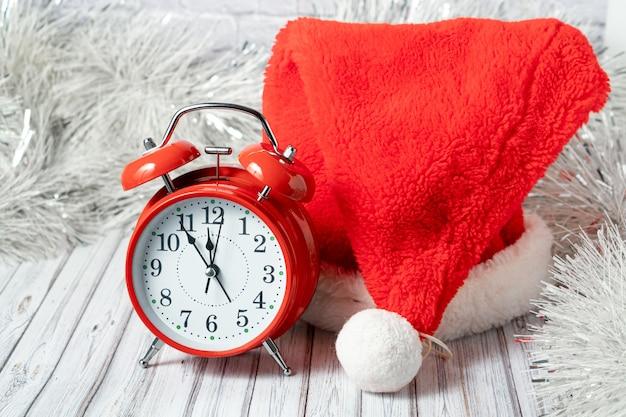 Czerwony vintage budzik i czapka świętego mikołaja na drewnianym stole ozdobionym girlandą i czerwonymi bombkami na nowy rok lub xmas. koncepcja usługi poczty, kuriera lub dostawy. skopiuj miejsce