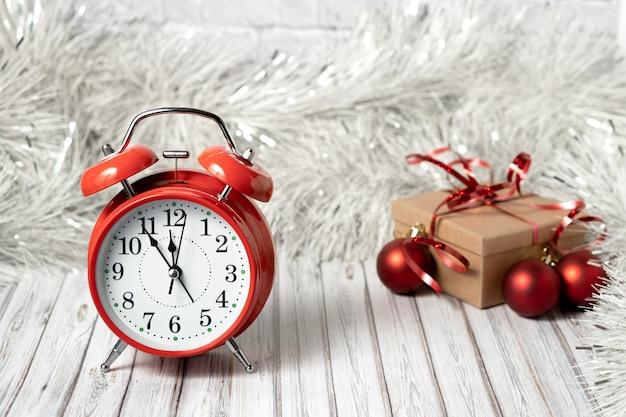 Czerwony vintage budzik i pudełko na drewnianym stole ozdobione girlandą i czerwonymi bombkami na nowy rok lub boże narodzenie. koncepcja usługi poczty, kuriera lub dostawy. skopiuj miejsce