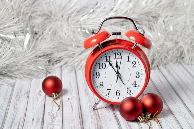 Czerwony vintage budzik na drewnianym stole ozdobionym girlandą i czerwonymi bombkami na nowy rok lub xmas. koncepcja usługi poczty, kuriera lub dostawy. skopiuj miejsce