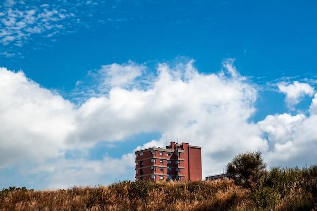 Czerwony wielokondygnacyjny budynek mieszkalny i zachmurzone niebo