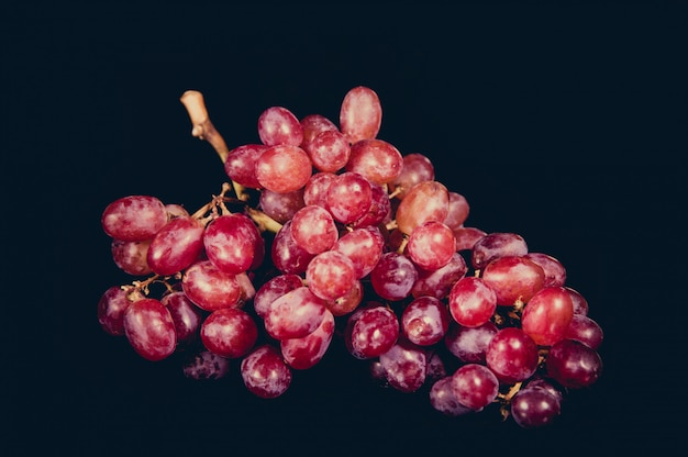 Czerwony winogrono odizolowywający na czarnym tle