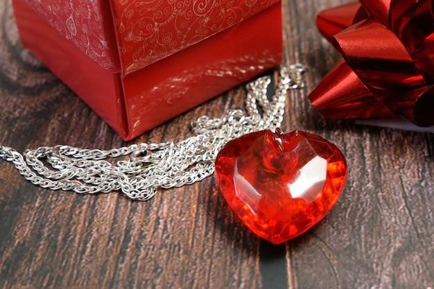 Czerwony wisiorek jako serce i pudełko na drewniane tła