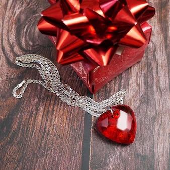 Czerwony wisiorek jako serce z łańcuchem w dłoni, zbliżenie