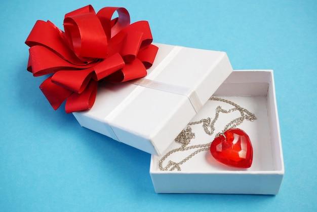 Czerwony wisiorek serce jako symbol walentynek w obecnym pudełku na niebiesko