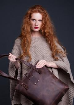 Czerwony włosiany moda model trzyma dużą ciemną rzemienną torbę na ciemnym tle. dziewczyna sobie sweter.