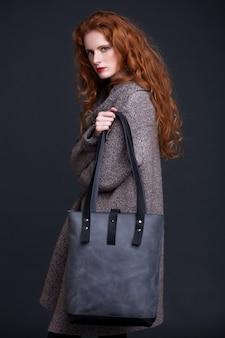 Czerwony włosiany moda model trzyma dużą ciemnoniebieską skórzaną torbę na ciemnym tle. dziewczyna sobie długi sweter.