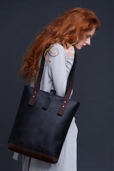 Czerwony włosiany moda model trzyma dużą ciemnoniebieską skórzaną torbę na ciemnym tle. dziewczyna ubrana w długi niebieski sweter.