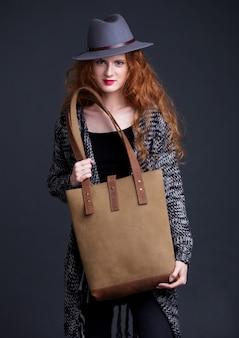 Czerwony włosiany moda model trzyma wielką rzemienną torbę na ciemnym tle. dziewczyna sobie sweter i kapelusz.