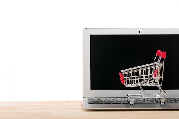 Czerwony wózek na zakupy na laptopie odizolowywającym na bielu.